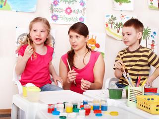 Children with teacher draw paints in play room. Preschool.