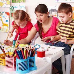 Children with teacher draw painting in play room. Preschool.