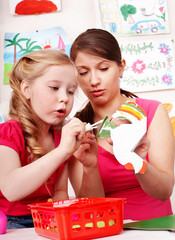 Child with teacher in play room. Preschool.
