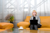 blonde woman with laptop in comfort hall