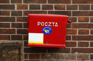 A standard red mailbox with mail