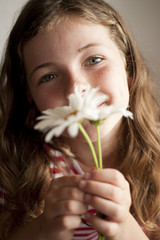 little girl smelling daisies