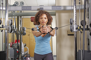 Woman doing standing rows in a gym