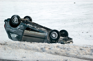 Car turned upside-down on slippery winter road
