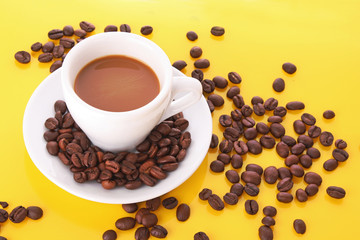 Small white cup of coffee with coffee grain on yellow background