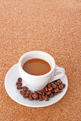 Small white  cup of coffee with coffee grain   on brown backgrou
