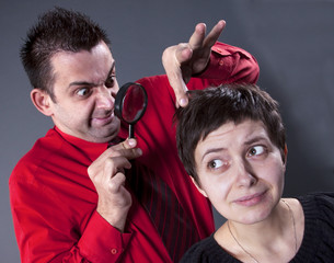 Man examining woman's hair with magnifying glass