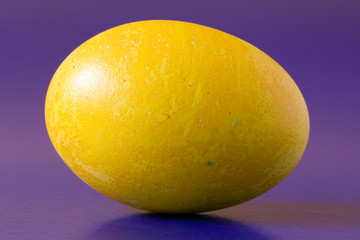 yellow  easter egg, isolated on purple background