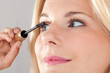 Beautiful woman applying mascara on her lashes