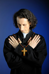 Praying priest with wooden cross.