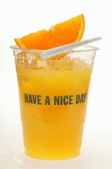 Orange juice in plastic tumbler with wedge of orange