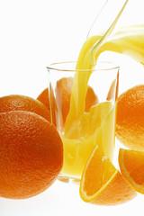 Pouring orange juice into glass among oranges