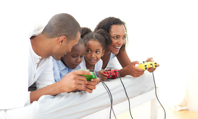 Lively family playing video game lying down on bed