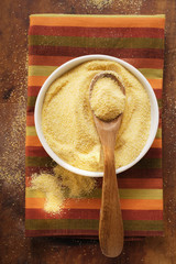 Polenta in bowl with wooden spoon on coloured cloth
