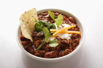 Chili con carne with cheese, sour cream and tortilla chips