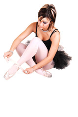 A young ballerina tying her ballet slippers.