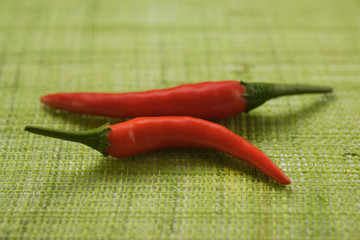 Two red chili peppers on green background