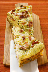 Two pieces of leek and bacon quiche on chopping board