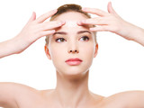 woman applying moisturizer cream on the forehead poster