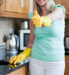 Smiling woman with thumb up cleaning a kitchen