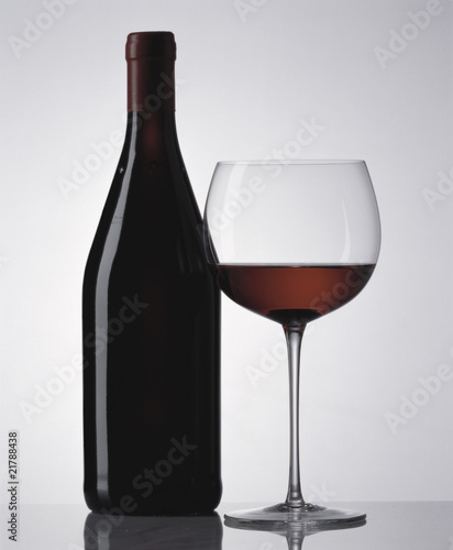 Glass of red wine and red wine bottle