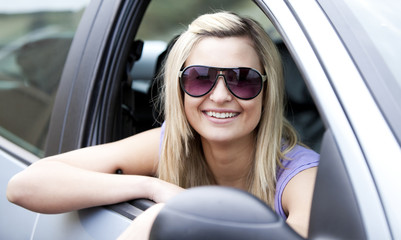 Jolly female driver wearing sunglasses sitting in her car