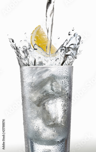 Pouring water into a glass with a wedge of lemon