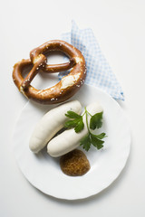 Two Weisswurst (white sausages) with pretzel and mustard