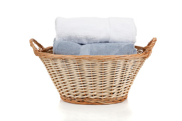 White and blue towels in a laundry basket on white