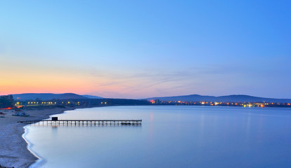 A night landscape of ocean with very smooth water and bridge