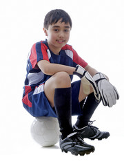 child sitting on a soccer ball