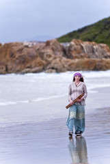 Attractive young woman walking at beach