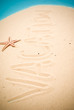 Vacation handwritten in sand