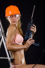 Girl in a helmet with a drill