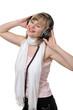 Junge freundliche Frau mit Schal hat Kopfhörer auf