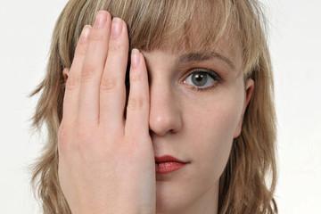 Junge freundliche Frau hält sich ein Auge zu