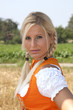 Frau in orangefarbenen Dirndl