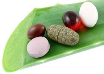 compléments alimentaires sur feuille d'aloe vera, fond blanc