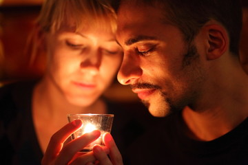 man and woman keeping glass candle. focus on man's left eye.