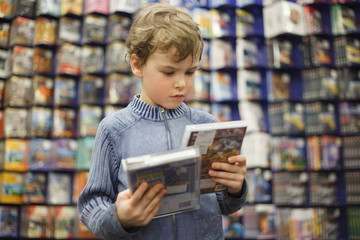 boy chooses one of two dvd in special store, ready contents