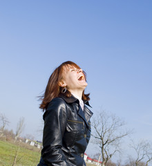 Girl laughing on the blue sky background