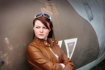 Pretty girl leaning against old airplane
