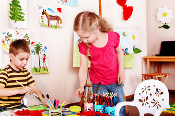 Children  draw paints in play room.