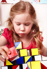 Child with block  in play room. Preschool.