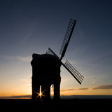 Silhouetted windmill on a hilltop at sunset poster