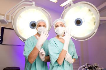 Surgeons putting on gloves