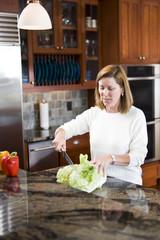 Woman in kitchen preparing vegetables