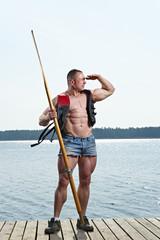 Muscular man with oar at lake watching