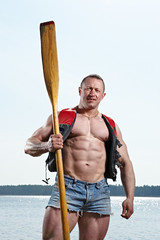 Muscular man with oar at lake