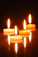 Burning candles isolated on black
